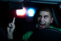 Pursuit police in of a man in the car who s showing them a middle finger selected focus on face Royalty Free Stock Image