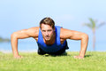 Push ups fitness man training push up outside in grass in summer fit male athlete working out cross exercising outdoor Stock Photos