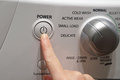 Pushing the power button of washing machine Stock Photography