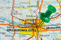 Pushpin in oklahoma city map highlighted with a green push pin on an atlas or Royalty Free Stock Images