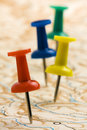 Pushpins on nameless map shot of colored geographic printed paper Stock Photo
