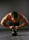 Pushups with kettlebell photo of a muscular asian man doing a Stock Photo
