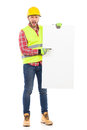 Put something on this placard manual worker in yellow helmet and reflective waistcoat holding white and pointing full length Royalty Free Stock Image