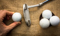 Putter and golfballs a hand holding a golf ball near a three other golf balls Royalty Free Stock Photos