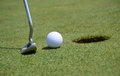Putting close a golf ball on the green into the hole Stock Images