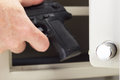 Putting firearm in gun safe person Royalty Free Stock Images