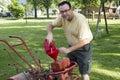 Putting gas in a old garden tiller older Stock Images