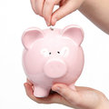 Putting money in piggy bank isolated on white Royalty Free Stock Photo