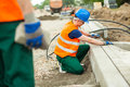 Putting paving stones young male construction worker Stock Photo