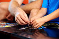Putting the pieces together father and son hands holding puzzle Royalty Free Stock Images