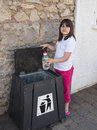 Putting rubbish in the bin young girl a Stock Photos