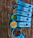 Puzzle effect Blue Measuring spoons with Spices on Wood Royalty Free Stock Photo