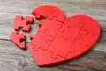 Puzzle heart red on grey wooden background Royalty Free Stock Photo