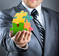 Puzzle house in hand businessman handling colorful Stock Photos