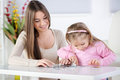 Puzzle mother and daughter playing at home they stacking jigsaw Royalty Free Stock Photo