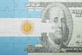 Puzzle with the national flag of argentina and dollar banknote Royalty Free Stock Photo