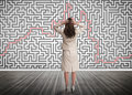 Puzzled businesswoman looking at a maze on wall Royalty Free Stock Images