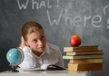 Puzzled student portrait of or schoolgirl siting at desk against blackboard Royalty Free Stock Photo