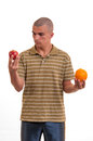 Puzzled young man confused choice between an apple an an orange he doesn t know what to Royalty Free Stock Photos