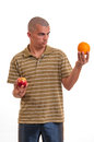 Puzzled young man confused what to choice between an apple an an orange he doesn t know Royalty Free Stock Photography