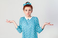 Puzzled young redhead girl with arms out, shrugging her shoulders, saying: who cares, so what, I don`t know.