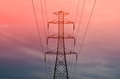 Pylon with power lines against orange sky - twilight Royalty Free Stock Photo
