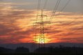 Pylon and power lines at sunrise with red sky sun Stock Images