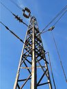 Pylon with wires under high voltage over the railway against the blue sky on a day Royalty Free Stock Photo