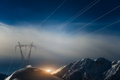 Pylons covered with snow in the high mountains carry energy downstream Stock Photo