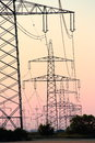 Pylons after sunset a double row of high voltage in front of reddened sky with the outlines of some bushes on the horizon Royalty Free Stock Photos