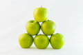 Pyramid of granny smith apples green stacked in a triangle or isolated Stock Images