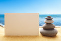 Pyramid of the stones with blank paper on the sandy beach at ocean background Stock Photography