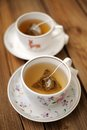 Pyramid tea bags brewed in two cups on wooden board Royalty Free Stock Image