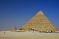 Pyramids and buses high in egypt with blue sky lots of with tourists Royalty Free Stock Photography