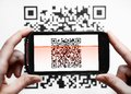 Qr code mobile scanner two hands holding a phone scanning a Royalty Free Stock Image