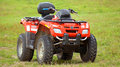 Quad atv red awd on green grass Stock Image