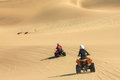 Quad driving people - two happy bikers in sand desert. Royalty Free Stock Photo
