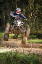 Quad rider jumping on a forest trail Stock Photography
