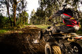 Quad rider jumping on a muddy forest trail Stock Photo