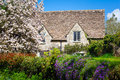 Quaint english country cottage stone surrounded by flowers in a rural village Stock Image