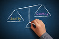 Quality and quantity balance hand with chalk is drawing scale on the chalkboard Stock Image