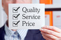 Quality service and price white card held in the hand of a businesswoman bearing text tick boxes with ticks in all three boxes Stock Photo