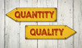 Quantity or quality direction signs on a wooden wall Stock Images