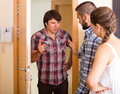 Quarrel with neighbour indoor young couple having serious talking angry at the door Royalty Free Stock Photo