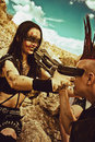 Quarrel on a post apocalyptic wasteland female merciless raider and male raider with mohawk haircut aiming each other with guns Stock Image