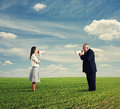 Quarrel between young woman and senior man women men in the field Royalty Free Stock Images
