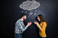 Quarrelling couple standing against background of chalkboard and screaming