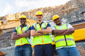Quarry workers group of standing next to excavator with arms crossed Royalty Free Stock Image