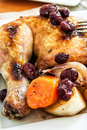 A quarter of roast chicken served with potato carrots and cranberry Stock Photos