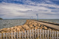 Quay with lamppost rocks and fence Royalty Free Stock Images